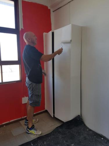 Jacques painting cupboards in library